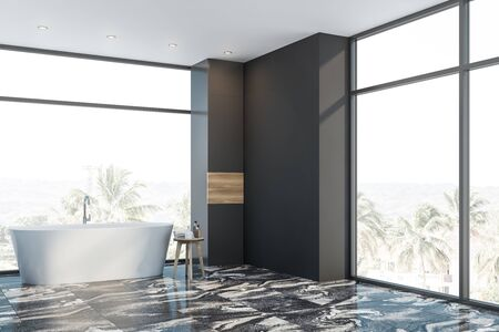 Interior of luxury bathroom with gray walls, black marble floor and comfortable bathtub near panoramic window with tropical view. 3d rendering