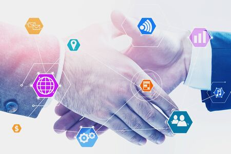 Close up of two business people shaking hands over white background with double exposure of colorful internet icons. Concept of hi tech and partnership. Toned image