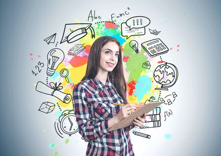 Portrait of smiling young woman with long brown hair wearing casual clothes and writing in clipboard standing near gray wall with education sketch Stock Photo