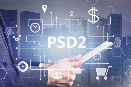 Side view of unrecognizable businessman in city holding tablet with double exposure of online shopping interface and PSD2 text. Concept of online payment and ecommerce. Toned image