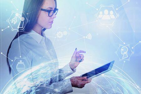 Jeune femme sérieuse avec tablette dans une ville floue avec double exposition de l'hologramme de la planète et de l'interface commerciale.