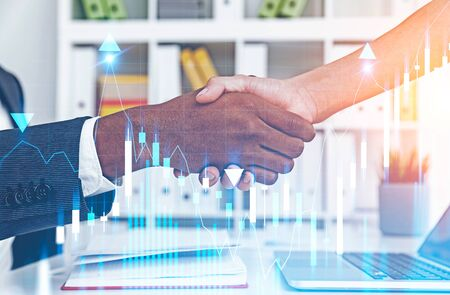 Close up of African American businessman and caucasian businesswoman shaking hands in blurred office with double exposure of graph. Concept of partnership and trading. Toned image Standard-Bild