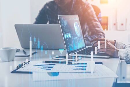 Business people working with laptops in blurred office with double exposure of business infographics and graphs. Market analysis concept. Toned image. Elements of this image furnished by NASA