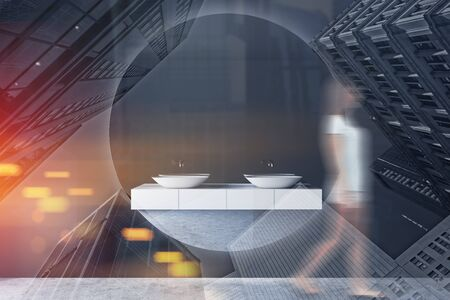 Young woman in casual clothes walking in luxury bathroom interior with gray walls, concrete floor, double sink standing on white countertop and large round mirror. Toned image double exposure blurred