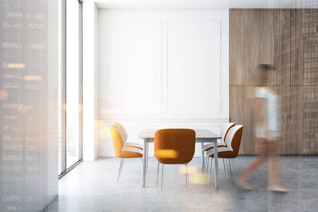 Woman in casual clothes walking in luxury minimalistic dining room interior with white and wooden walls, concrete floor and long table with orange chairs. Toned image double exposure blurred