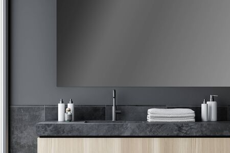 Close up of bathroom sink with large mirror above it standing in stylish room interior with grey and tile walls. 3d rendering Stockfoto