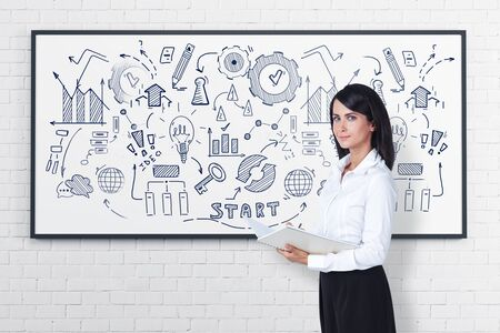 Smiling young woman with notebook standing near whiteboard with business plan sketch drawn on it. Concept of business and education.