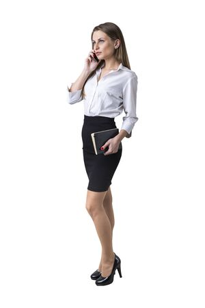 Isolated full length portrait of serious young blonde businesswoman talking on smartphone and holding planner. Concept of communication
