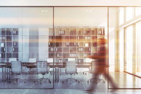 Junger Geschäftsmann, der in der Bürohalle mit weißen Wänden und einem komfortablen Konferenzraum mit Holztisch und Bücherregalen spaziert. Getöntes Bild verschwommen