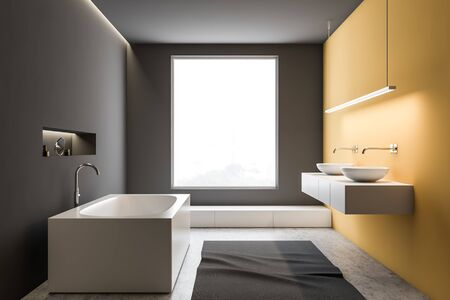 Interior of stylish bathroom with gray and yellow walls, concrete floor, comfortable angular bathtub and double sink standing on white countertop. 3d rendering 写真素材
