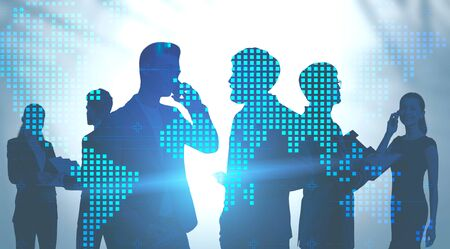 Silhouettes of business people over blurred background with double exposure of world map. Concept of teamwork and international business. Toned image 写真素材
