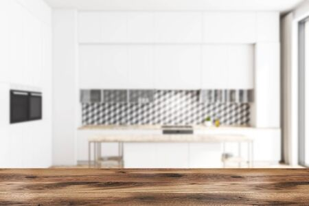 Blurred interior of stylish kitchen with geometric pattern wall, white countertops with built in sink and oven, white cupboards and island. Table for your product in foreground. 3d rendering