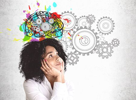 Smiling young African American woman in white shirt looking at colorful brain sketch with gears drawn on concrete wall. Concept of brainstorming Stok Fotoğraf