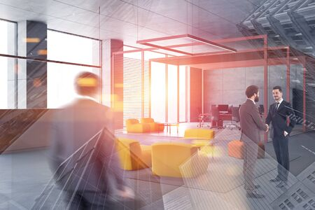 Business people shaking hands and walking in modern open space office with reception and lounge area. Concept of business lifestyle. Toned image double exposure blurred Stockfoto