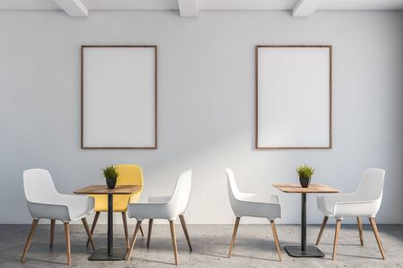 Interior of minimalistic cafe in hotel or business center with white walls, stone floor, two square tables with white and yellow chairs and two vertical mock up poster frames. 3d rendering