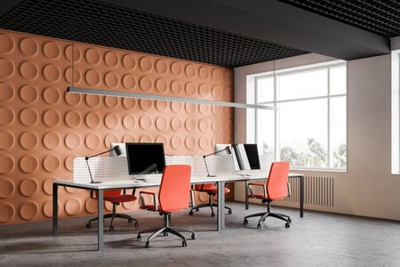 Corner of stylish open space office with bright orange geometric pattern walls and stylish white computer tables with orange chairs. 3d rendering Stockfoto