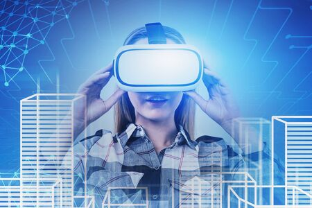 Astonished blonde young woman in VR glasses looking at virtual city with network interface. Concept of hi tech and future technology. Toned image double exposure Zdjęcie Seryjne