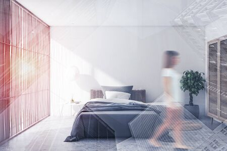 Young woman walking in stylish bedroom with white walls, comfortable bed with gray blanket and wooden wardrobe. Toned image double exposure blurred Banco de Imagens