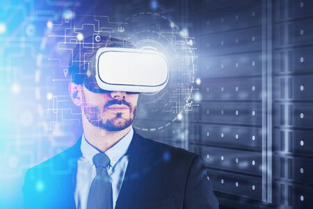 Bearded caucasian man in suit wearing VR glasses with double exposure of HUD hi tech interface in server room. Concept of software development. Toned image blurred