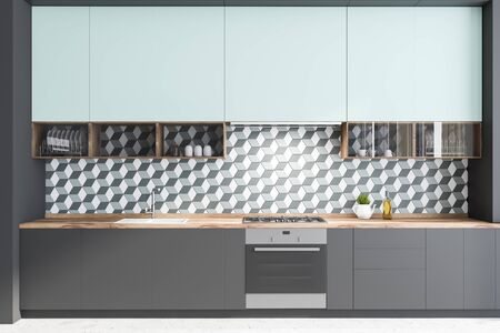 Interior of minimalistic kitchen with geometric pattern walls, concrete floor, gray countertops with built in oven, cooker and sink and blue cupboards. 3d rendering