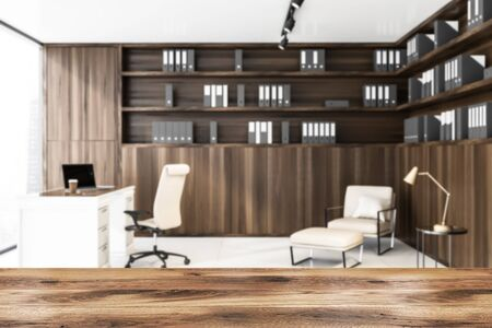 Blurred interior of luxury CEO office with wooden bookcase with folders, comfortable table with laptop and lounge area with beige armchair. Table for your product in foreground. 3d rendering Zdjęcie Seryjne