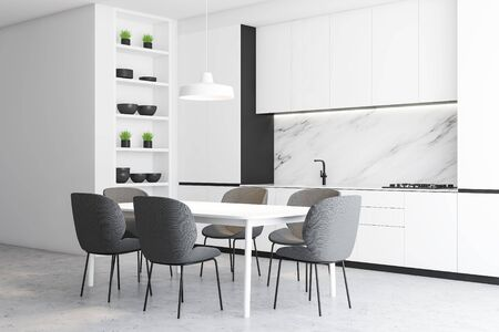 Corner of minimalistic luxury kitchen with white walls, concrete floor, white countertops with built in cooker and sink and white cupboards. Comfortable dining table with gray chairs. 3d rendering