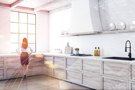 Woman in formal clothes standing in stylish kitchen interior with white walls, wooden floor and wooden countertops with built in sink and cooker. Toned image double exposure Stock fotó