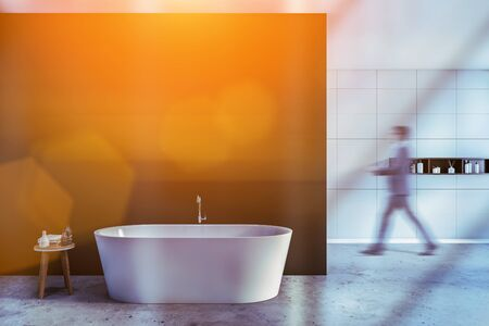 Man walking in spacious modern spa bathroom with white and gray walls, comfortable bathtub and shelf with shampoos and creams. Toned image blurred Stock fotó