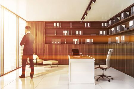 Young businessman standing in luxury wooden CEO office with wooden bookcase, lounge area and white table with laptop. Concept of leadership. Toned image Stockfoto