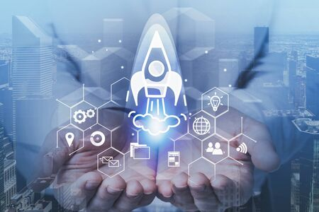 Hands of man holding startup rocket hologram with double exposure of cityscape. Concept of business idea. Banco de Imagens