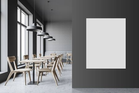 Interior of minimalistic cafe with gray walls, concrete floor, comfortable sofa and wooden tables with chairs. Vertical mock up poster on the wall. 3d rendering