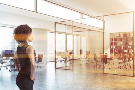 Gorgeous and smart African American businesswoman standing in modern office with white walls, open space area and meeting room with glass walls. Corporate lifestyle concept. Toned image