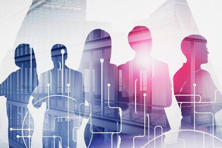 Silhouettes of business people over skyscraper background with double exposure of network interface. Concept of teamwork and hi tech. Toned image Stock Photo