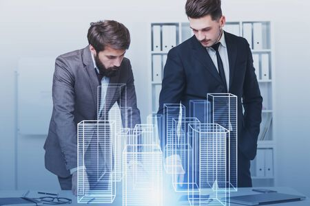 Two young caucasian architects working with city hologram in white office. Concept of hi tech and real estate market. Toned image double exposure