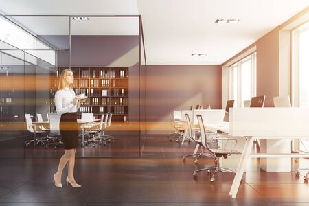 Pensive blonde businesswoman with coffee standing in modern open space office with gray walls, white computer desks and meeting room behind glass walls. Toned image