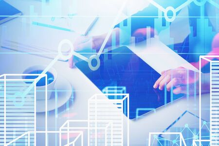 Hands of businessman working with tablet in office with double exposure of virtual cityscape and digital graph. Concept of real estate market and hi tech. Toned image Imagens