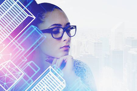 Beautiful thinking young woman in glasses standing in modern city with double exposure of smart city interface. Concept of hi tech and computer engineering. Toned image Imagens