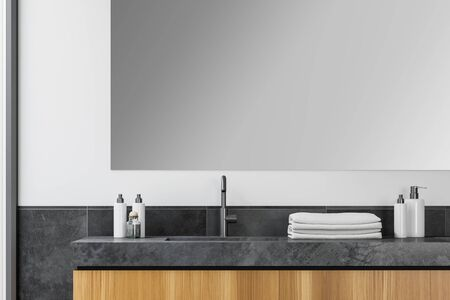 Close up of bathroom sink with large mirror above it standing in stylish room interior with white and gray tile walls. 3d rendering Banco de Imagens