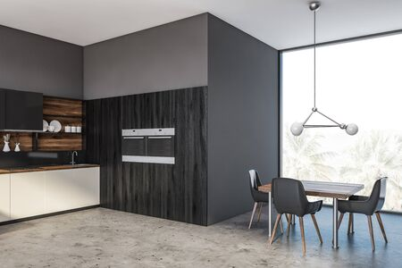 Corner of panoramic kitchen with gray walls and floor, white countertops, black cupboards, two built in ovens and square table with black chairs. 3d rendering Zdjęcie Seryjne