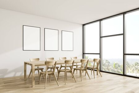 Corner of modern dining room with white walls, wooden floor, panoramic window and long wooden table with three vertical mock up posters. 3d rendering