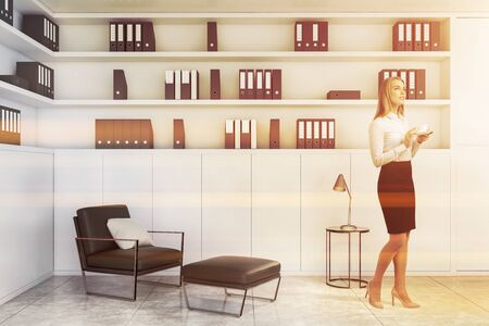 Pensive blonde businesswoman with coffee standing in office lounge with white bookcase and comfortable black leather armchair. Corporate lifestyle concept. Toned image Stockfoto