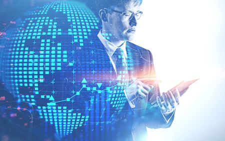 Serious young caucasian businessman in glasses using tablet computer with double exposure of planet hologram and network interface. Concept of hi tech. Toned image