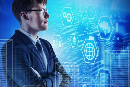 Confident young caucasian man in glasses looking at hi tech interface with city hologram. Concept of software development and smart city. Toned image double exposure Stock Photo