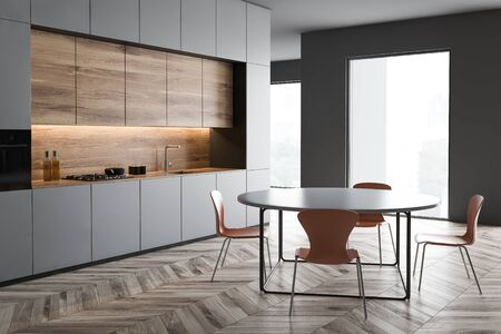 Corner of loft kitchen with gray walls, wooden floor, gray countertops, wooden cupboards and round dining table with orange chairs. 3d rendering 写真素材