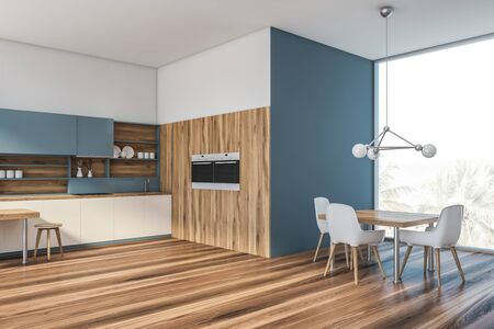 Corner of panoramic kitchen with white and blue walls, wooden floor, white countertops, blue cupboards, two built in ovens and square table with white chairs. 3d rendering
