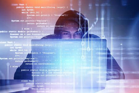 Young African American hacker in black hoodie working with laptop with double exposure of lines of code. Concept of cyber security and identity theft. Toned image