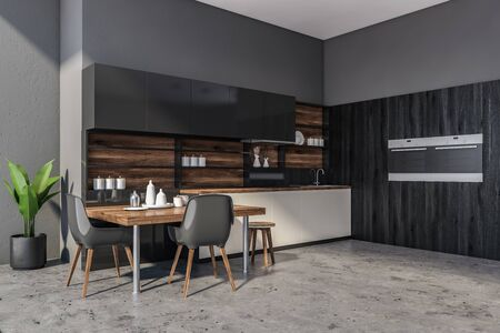 Corner of modern kitchen with concrete walls and floor, white countertops, black cupboards, two built in ovens and stylish table with black chairs. 3d rendering