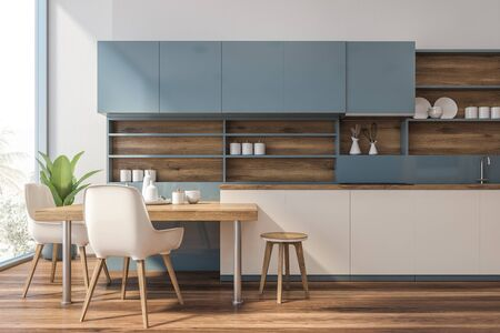 Interior of modern kitchen with white walls, wooden floor, white countertops, blue cupboards and stylish table with white chairs. 3d rendering