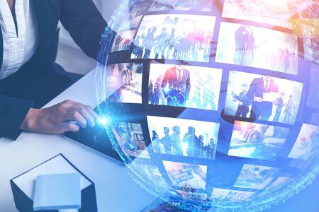 Donna che utilizza tablet sul tavolo dell'ufficio con doppia esposizione dell'interfaccia di streaming video futuristica. Concetto di alta tecnologia e social media. Immagine tonica