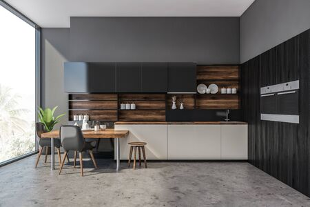 Interior of modern kitchen with concrete walls and floor, white countertops, black cupboards, two built in ovens and stylish table with black chairs. 3d rendering 写真素材